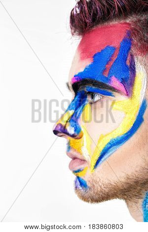 portrait of young attractive man with colored face paint on a white background. Professional Makeup Fashion. fantasy art makeup