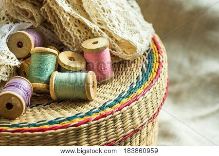 Woven rattan crafts and sewing supply box wooden spools rolls of lace linen cloth background hobby fashion concept close up