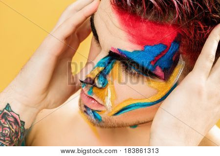 portrait of young attractive man with colored face paint on a yellow background. Professional Makeup Fashion. fantasy art makeup