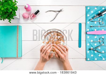 Beautiful woman's hands with perfect manicure in bowl of water on wooden background. Top view. Copy space. Nail Care.