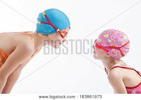 Two sisters in bathing suits look at each other In swimming goggles
