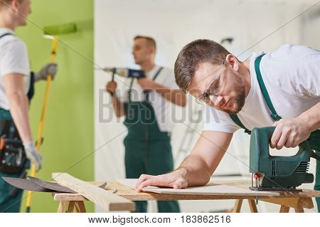 Three Workers Renovating A Room