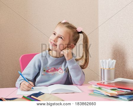 girl writing with pen at the table