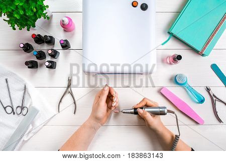 woman hands making manicure to herself on wooden background. Top view. Copy space. Nail Care.