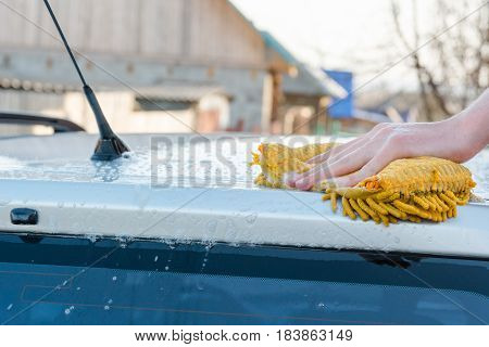 The Man Washes With A Sponge With Foam The Car
