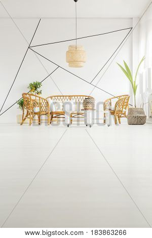 White living room with rattan furniture and decorative wall tape