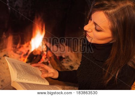 Pretty woman reading the book sitting near the hearth