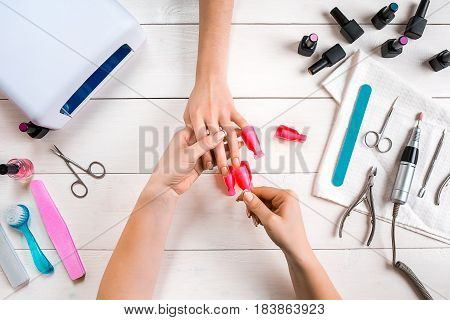 Nail care. Closeup of female hands filing nails with professional nail file in beauty nail salon. Close-up of beautician hands doing perfect manicure on woman's hands. Nail hygiene. Top view