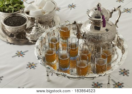Traditional festive Moroccan silver tea set and glasses on the table