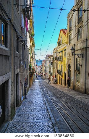 Steep narrow street of Lisbon with cable car rails in the middle and ocean in the background