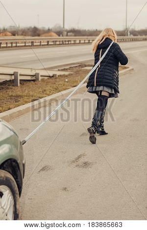Auto assistance and insurance troubles while traveling concept. Woman pulling broken car on road