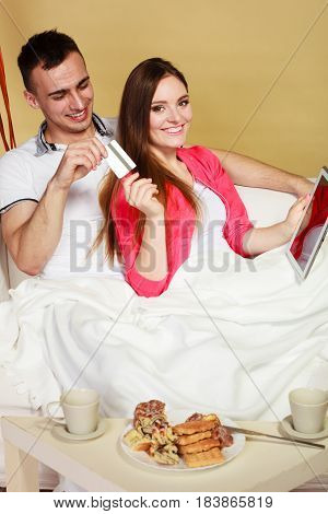 Young Couple With Tablet And Credit Card At Home