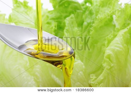olive oil being pouring in a spoon