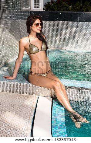 Beautiful young woman in bikini sitting on the edge of the swimming pool. Jacuzzi. Resort