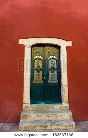 Red colonial building with an interesting door in Valladolid Mexico