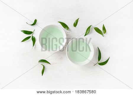 Two cups of green tea surrounded with fresh tea leaves view from above composition