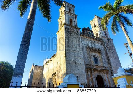 Cathedral in Valladolid Mexico with palm trees on either side