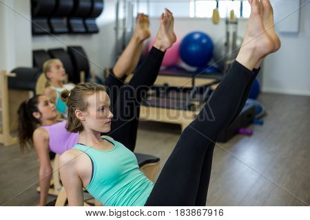 Fit woman exercising on wunda chair in gym