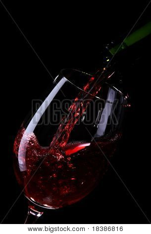 wine being poured into a glass on black