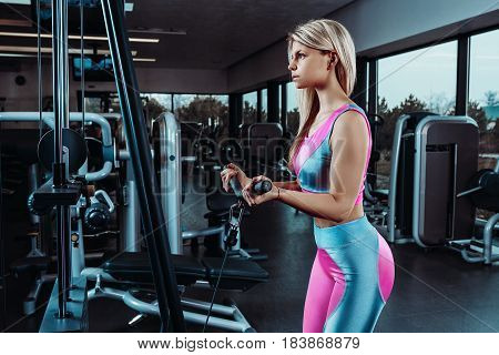 Young fitness woman execute exercise with exercise-machine Cable Crossover in gym, horizontal photo. Muscular
