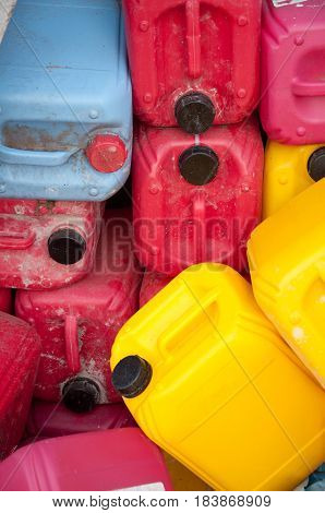 Pile of red yellow blue dirty plastic canisters for bulding priming. Vertical photo