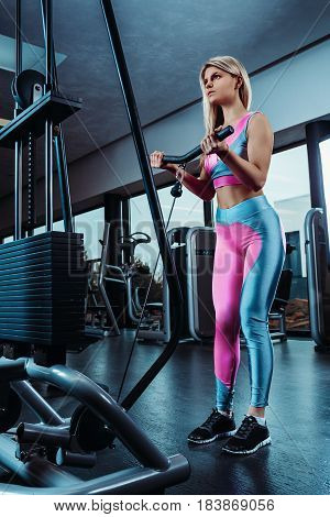 Young fitness woman execute exercise with exercise-machine Cable Crossover in gym. Vertical photo. Muscular
