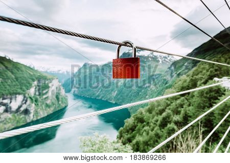 Tourism vacation and travel. Red love lock padlock on bridge and mountains view over magical Geirangerfjorden from Flydalsjuvet viewpoint Norway Scandinavia. poster