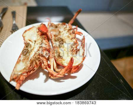 Giant grilled river prawns on the white dish.