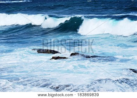 Bright blue ocean waves with whitecaps on a windy day