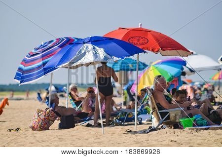 Rehoboth Beach USA - July 30 2013: People resting on beach under umbrellas on sunny summer day in Delaware