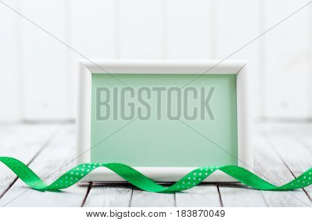 Empty card with green ribbon on the white wooden background.