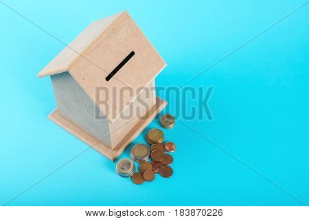 The concept of financial savings to buy a house. Money box and coins isolated on the blue background.