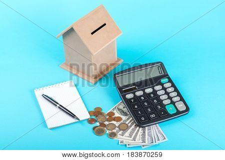 The concept of financial savings to buy a house. Money box dollars coins and calculator isolated on the blue background.