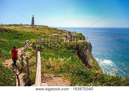 People walking down the path on the edge of the cliff in Cape Roca, Portugal with view of Atlantic ocean
