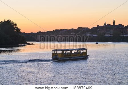 Washington DC USA - August 14 2013: American River Taxi boat on Potomac river with skyline of Georgetown during sunset