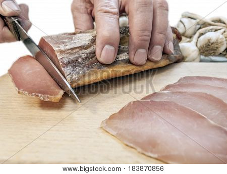 Man cutting smoked sirloin with garlic on a table