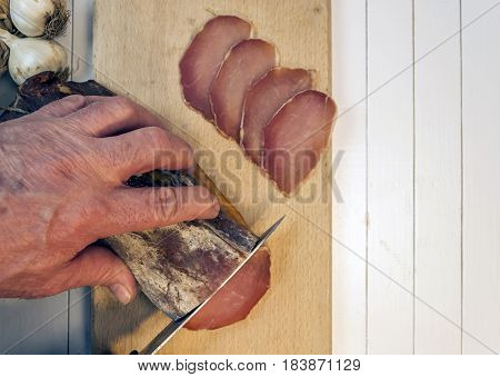 Man cutting smoked sirloin with garlich on a white wooden table