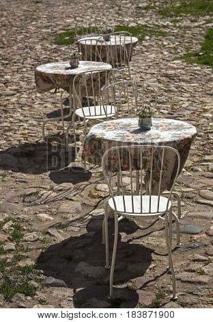 Tables and chairs outdoor cafe. Stone pavement