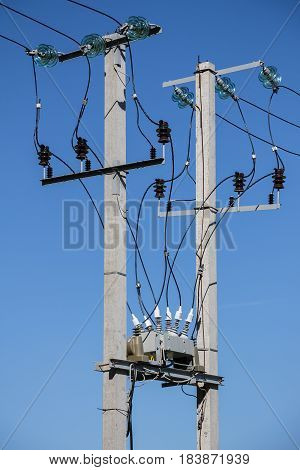 Power line supports. Insulators junction box on background of blue sky poster