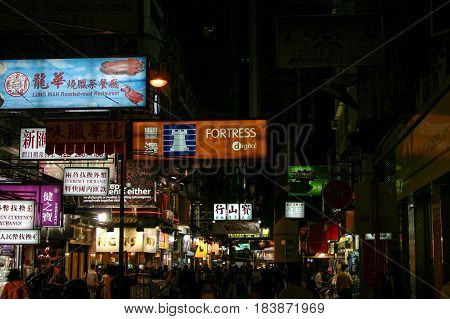 HONG KONG CHINA - 29 DECEMBER 2005 - Typical night time scene of a crowded Hong Kong street full of shoppers. Vibrant with colorful neon signs for shops restaurants and businesses.
