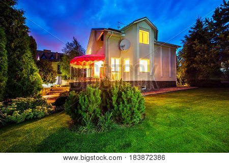 Horizontal view of single-family home with patio. Mansion. Evening time. Yellow light from windows