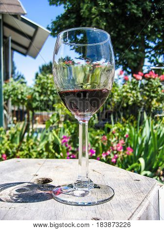 Closeup of glass of red wine on table in outside garden in Napa Valley