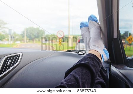 Girl foot over a car dashboard in transit wearing white and blue socks.