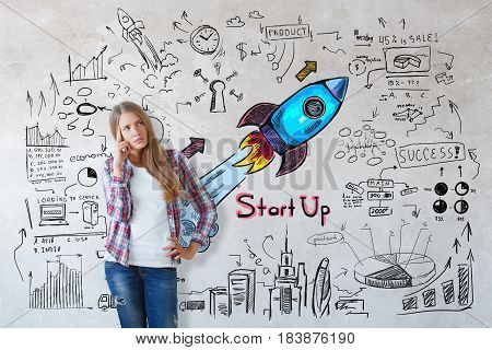 Thoughtful young european woman on concrete background with colorful business sketch. Research and startup concept