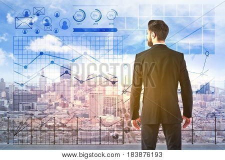 Back view of young businessman standing on rooftop with city view and abstract digital business charts. Finance concept