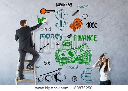 Worried young woman and businessman on ladder drawing colorful business sketch on concrete background. Money concept