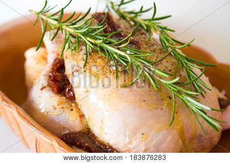 Raw whole chicken with rosemary and dried tomato