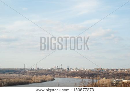 A huge processing plant in the distance, river and cloudy sky, the concept of ecological disaster, the emission of carbon dioxide into the atmosphere