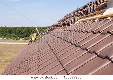 House under construction. Roofing tiles with open skylights. A worker installs skylights.