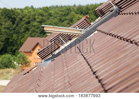 Closeup of new roof with skylight and natural red tile